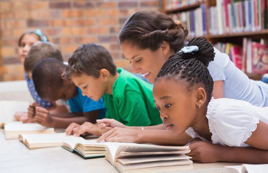 Children reading with their teacher.