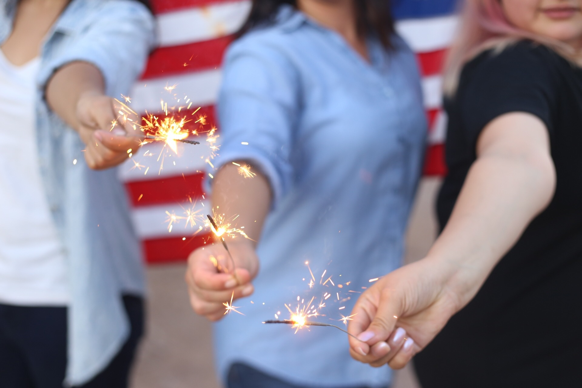 Group of people holding sparklers with The Spirit of Independence Day